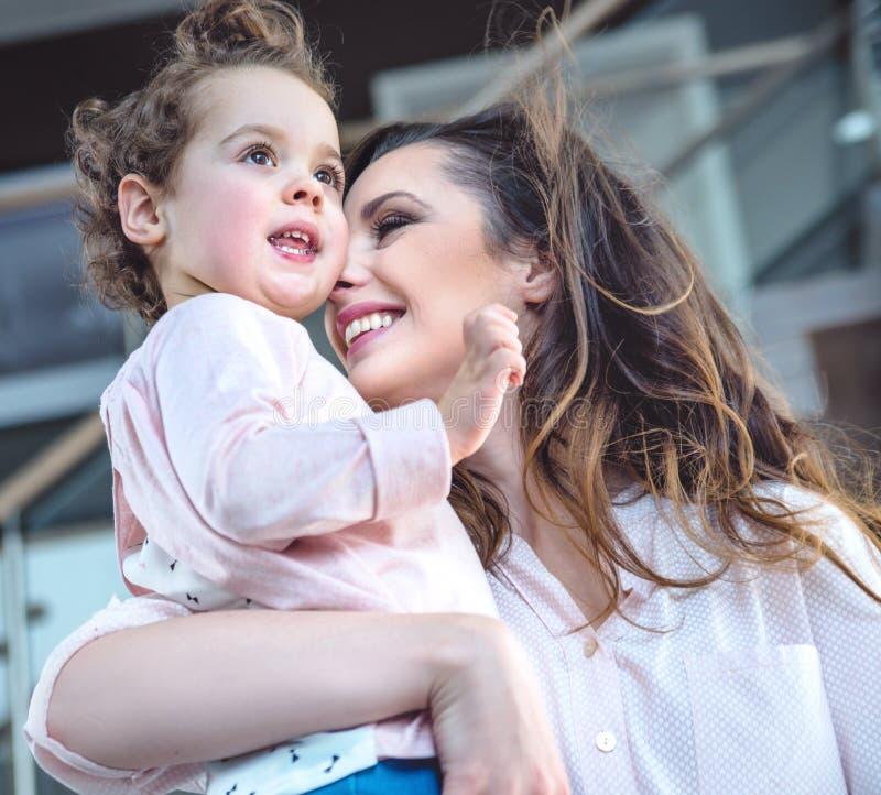 一个快乐的妈妈拥抱的心爱的孩子的画象 库存图片