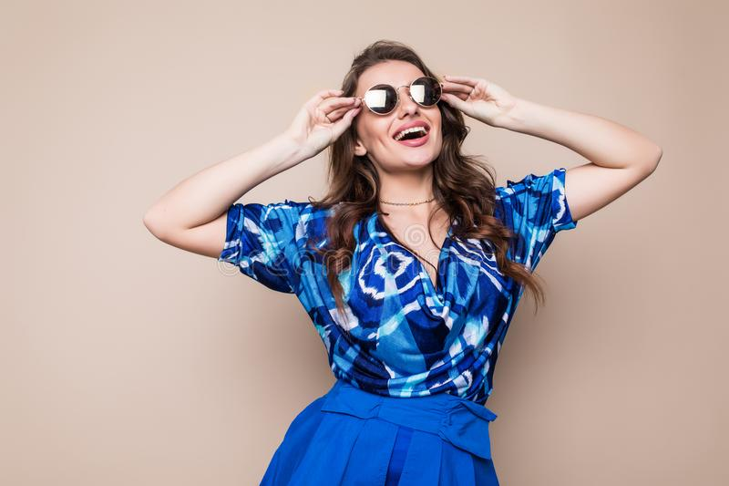 一个快乐的少妇的画象在蓝色看照相机的礼服和太阳镜穿戴了被隔绝在棕色背景 免版税图库摄影