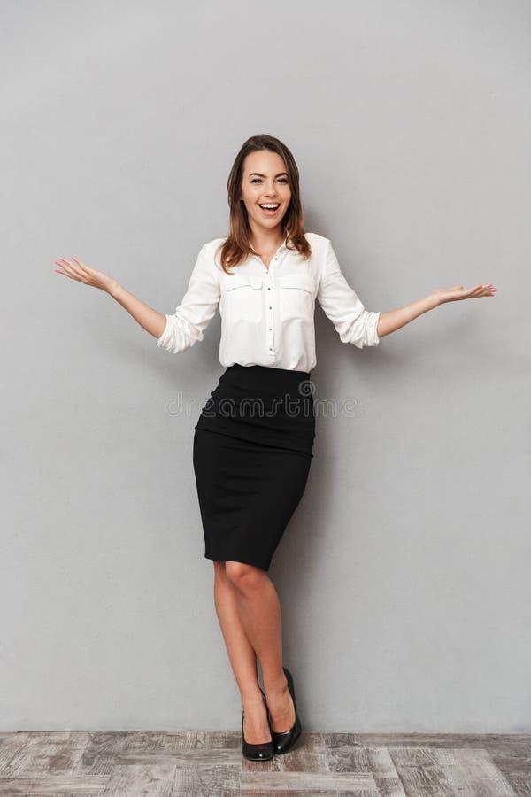 一个快乐的年轻女商人的全长画象 免版税库存图片