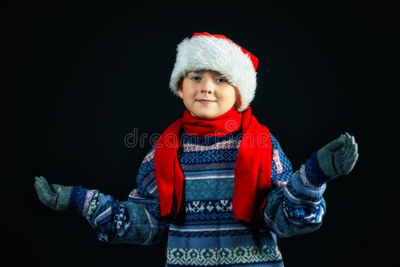 一个快乐的男孩的演播室画象圣诞老人的帽子的 免版税库存照片