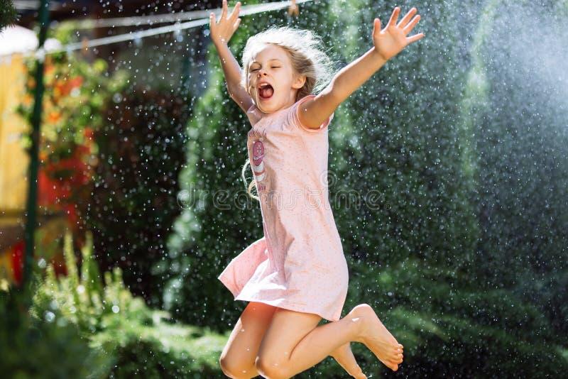 一个快乐的迷人的七岁的女孩享受一个晴朗的夏天早晨并且在家获得乐趣在庭院里 库存照片