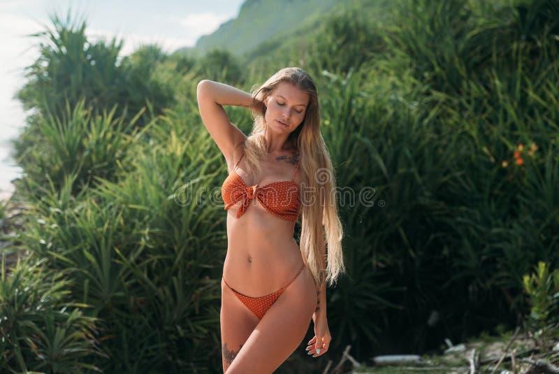 一个性感的女孩获得在海滩的乐趣,享用温暖的沙子 游泳衣的女孩盖了她的眼睛与 免版税库存图片
