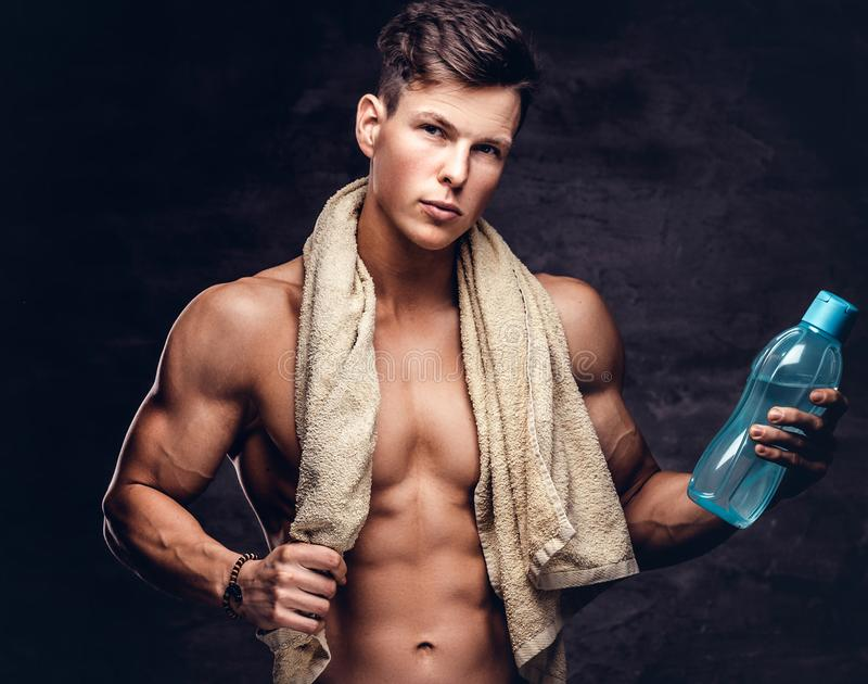 一个性感的赤裸上身的年轻人模型,举行毛巾和瓶的画象与强健的身体和时髦的理发的a 库存图片