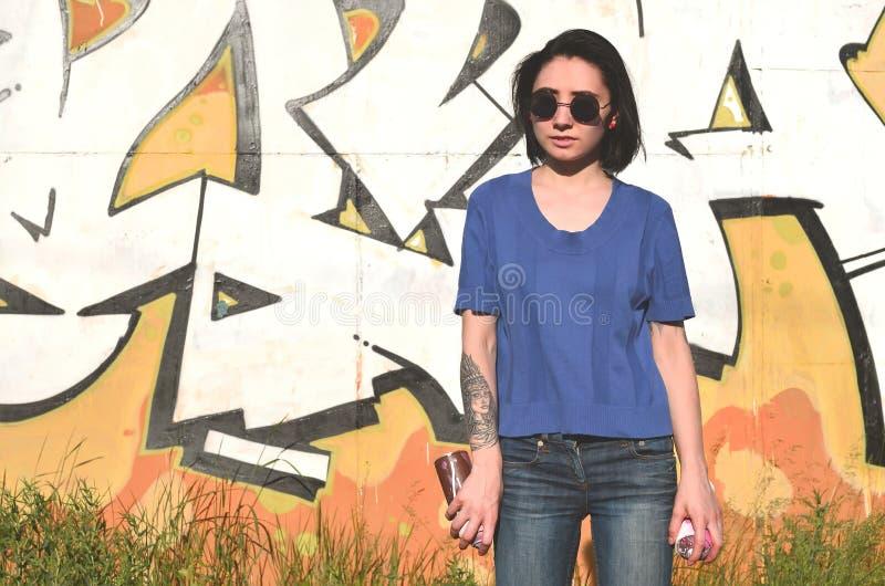 一个情感女孩的画象有黑发和穿甲的 一个女孩的照片有湿剂油漆罐头的在街道画的手上 免版税库存图片