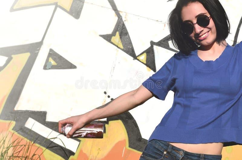 一个情感女孩的画象有黑发和穿甲的 一个女孩的照片有湿剂油漆罐头的在街道画的手上 免版税库存照片
