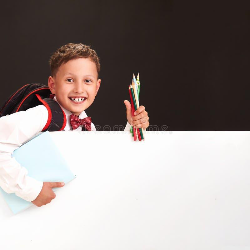 一个情感孩子的画象 男孩男小学生微笑,愉快返回到学校 关于学生的概念 拿着白色横幅 免版税库存图片