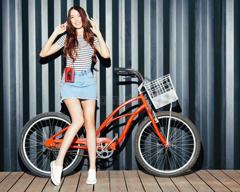 一个惊人的长腿的女孩、一名亚裔妇女夏天成套装备的,一条牛仔布裙子,有卡式磁带播放机和耳机的 免版税库存照片