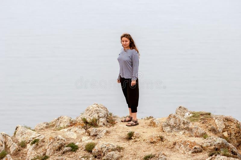 一个惊奇的美女站在水上的岩石上 免版税库存照片