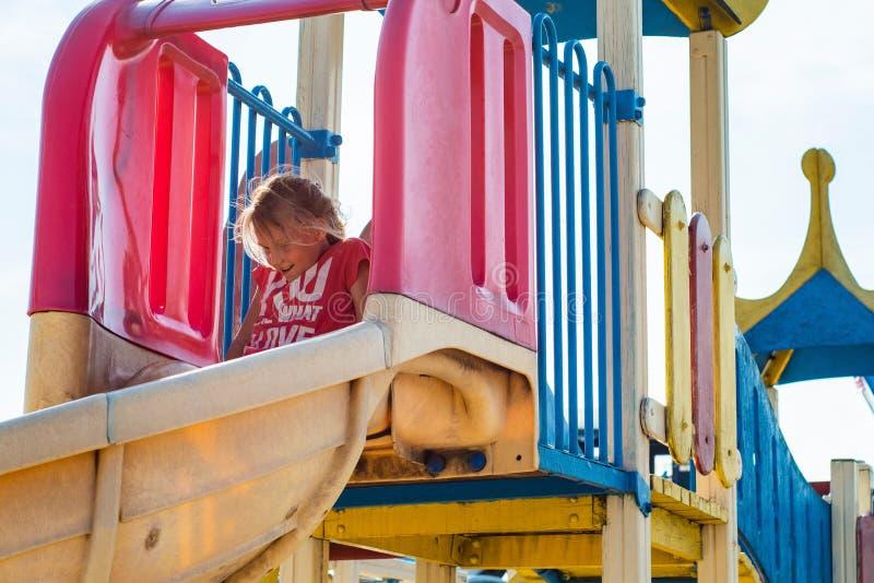 一个愉快和快乐的女孩在儿童` s过山车乘坐在公园 免版税图库摄影