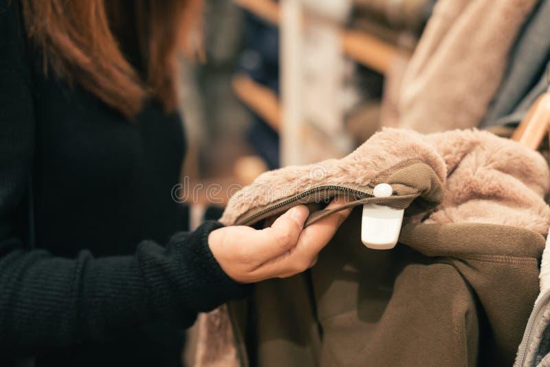 一个愉快的亚裔少妇的半身体射击有看衣裳的书包的垂悬在衣物商店里面的路轨 免版税图库摄影