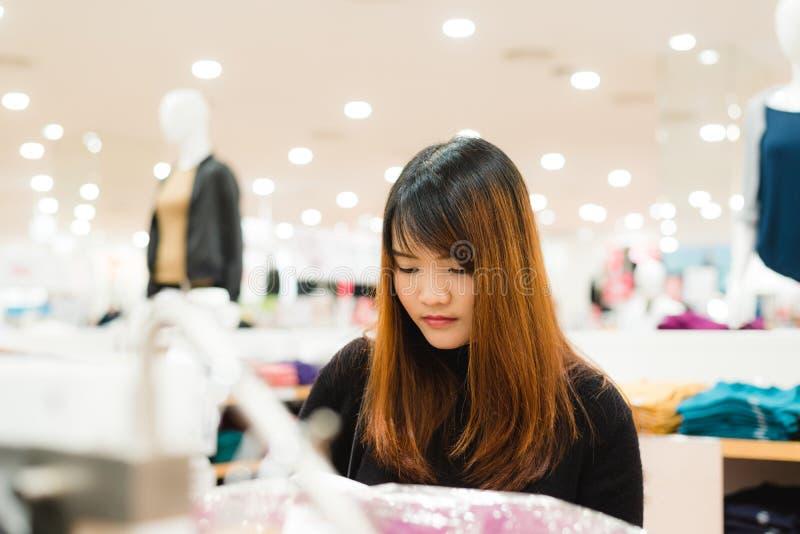 一个愉快的亚裔少妇的半身体射击有看衣裳的书包的垂悬在衣物商店里面的路轨 库存图片