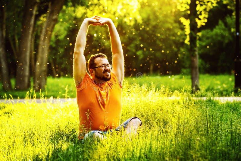 一个愉快的人在与半眯着眼睛看的眼睛的绿草舒展自己 免版税库存照片