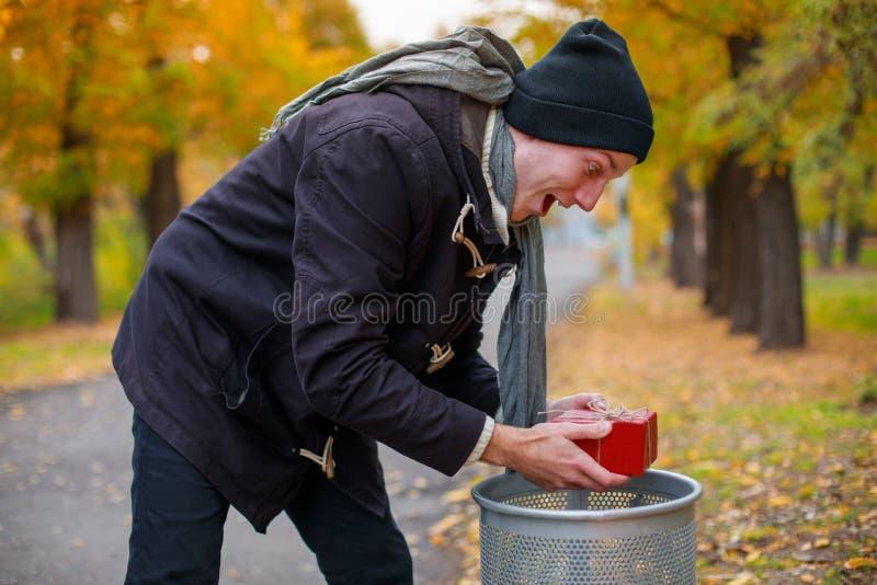 一个愉快的人在公园发现了在一个垃圾箱的一个礼物盒并且是愉快的 库存图片
