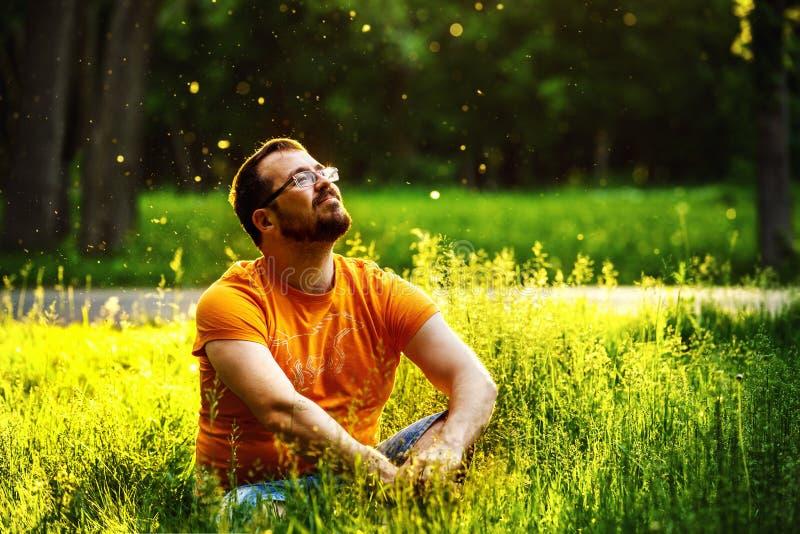 一个愉快的体贴的梦想家人坐绿草在公园 免版税库存照片