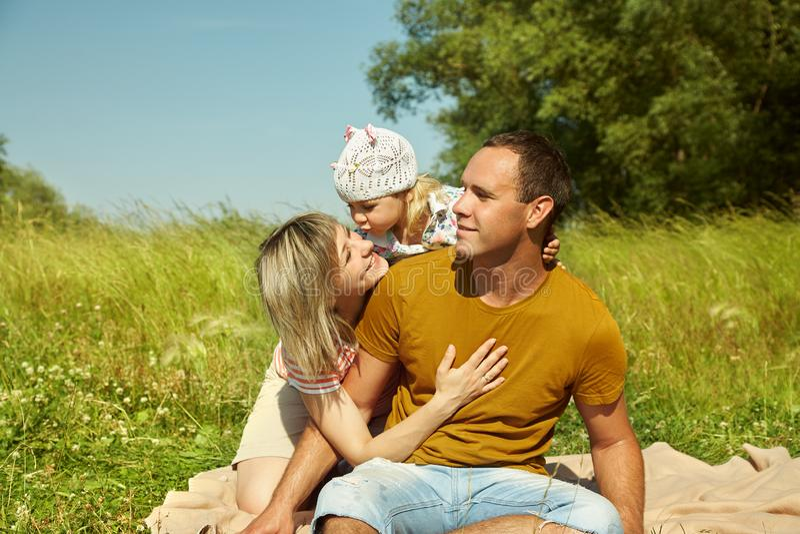 一个愉快的使用的家庭的画象户外 有女儿的父母在夏天 妈妈、爸爸和孩子 免版税图库摄影