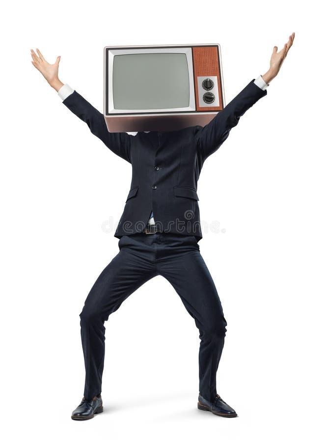 一个愉快的商人在胜利行动的白色背景站立,当佩带在他的头时的一个减速火箭的电视箱子 免版税库存照片