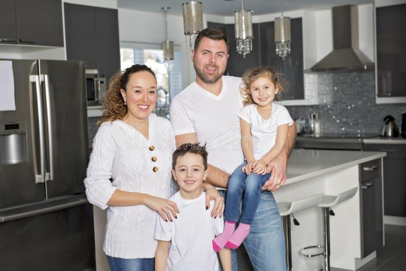 一个愉快的四口之家的画象在厨房里在家 免版税库存图片