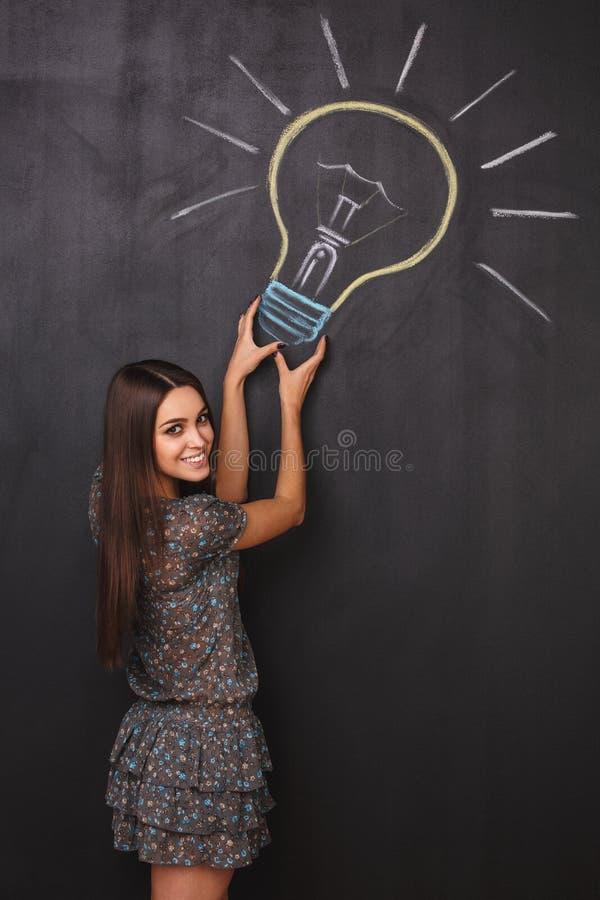 一个愉快的女孩有一个好主意 在黑板的一个电灯泡 抓住的概念想法 免版税库存照片
