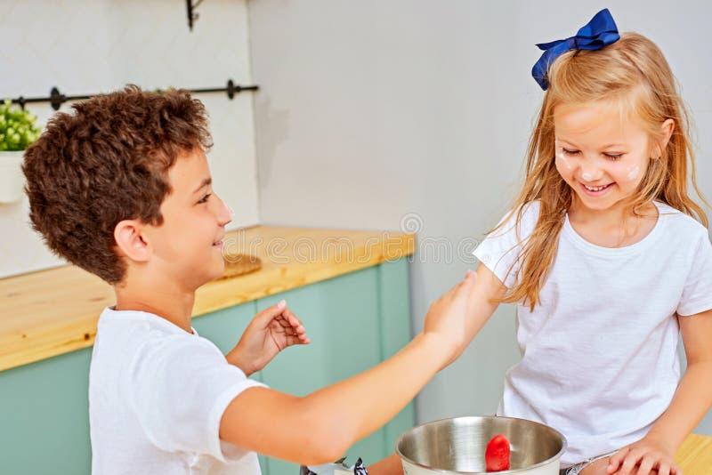 一个愉快的女孩的画象有面粉鼻子的在有近她的兄弟的厨房里 免版税库存图片