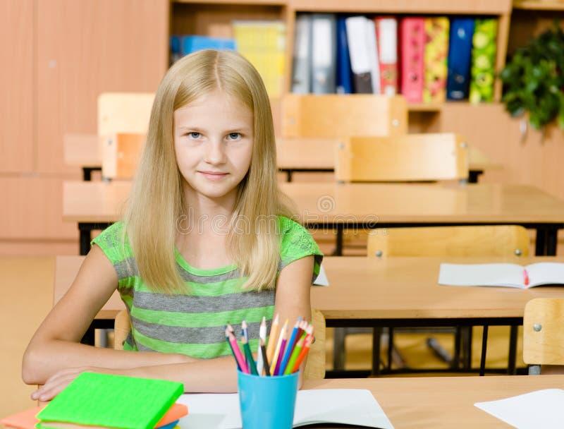 一个愉快的女孩的画象在教室 免版税图库摄影