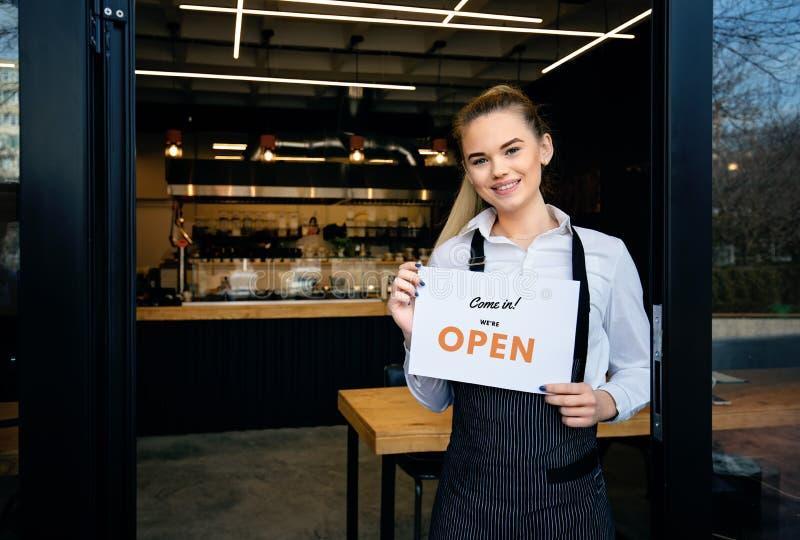 一个愉快的女服务员身分的画象在餐馆入口的 年轻女服务员画象参加新的顾客 开放妇女的陈列 库存图片