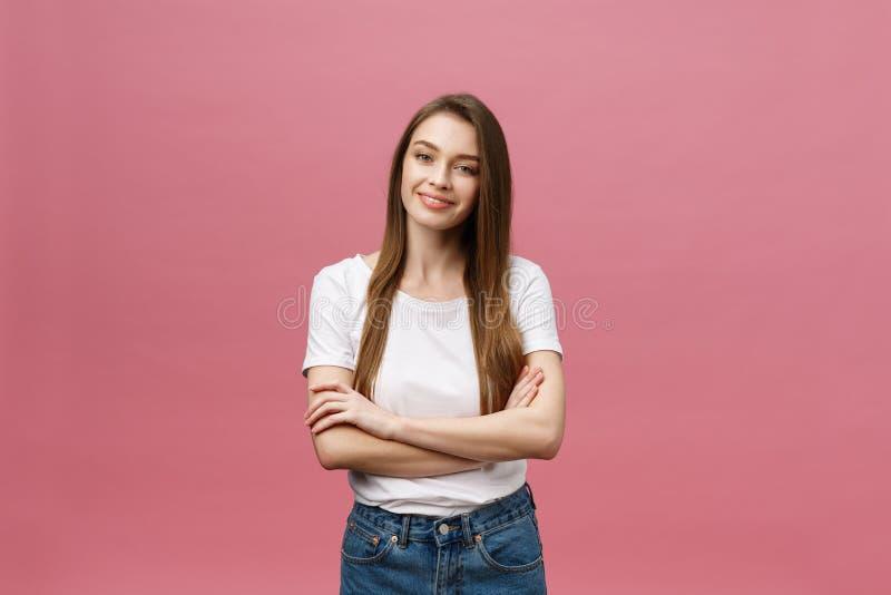 一个愉快的妇女身分的画象与胳膊的在桃红色背景折叠了隔绝 库存图片