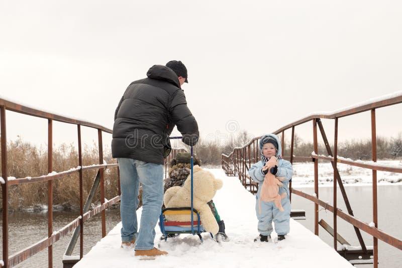 一个愉快的孩子以冬天时尚在他的村庄房子庭院给摆在与玩具猪穿衣 第一雪,家庭,传统 免版税库存照片