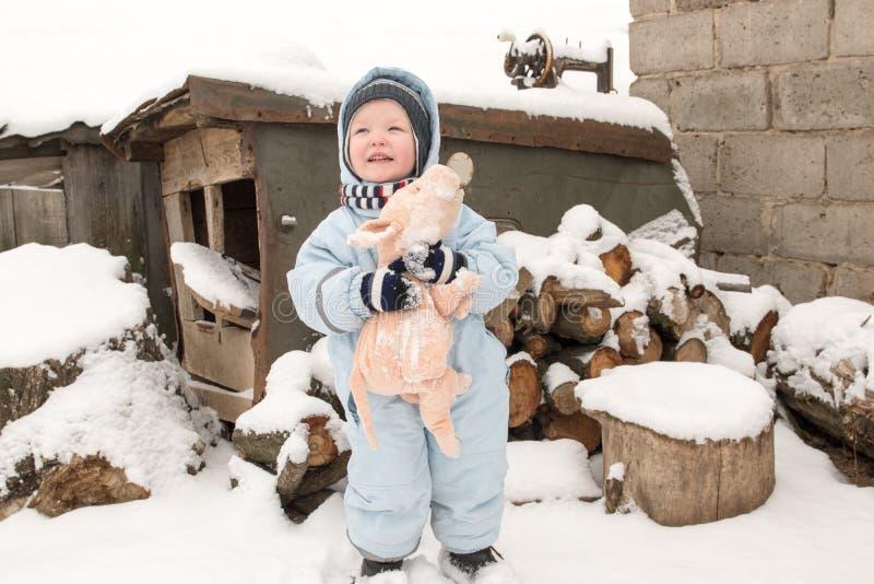 一个愉快的孩子以冬天时尚在他的村庄房子庭院给摆在与玩具猪穿衣 第一雪,家庭,传统 免版税库存图片