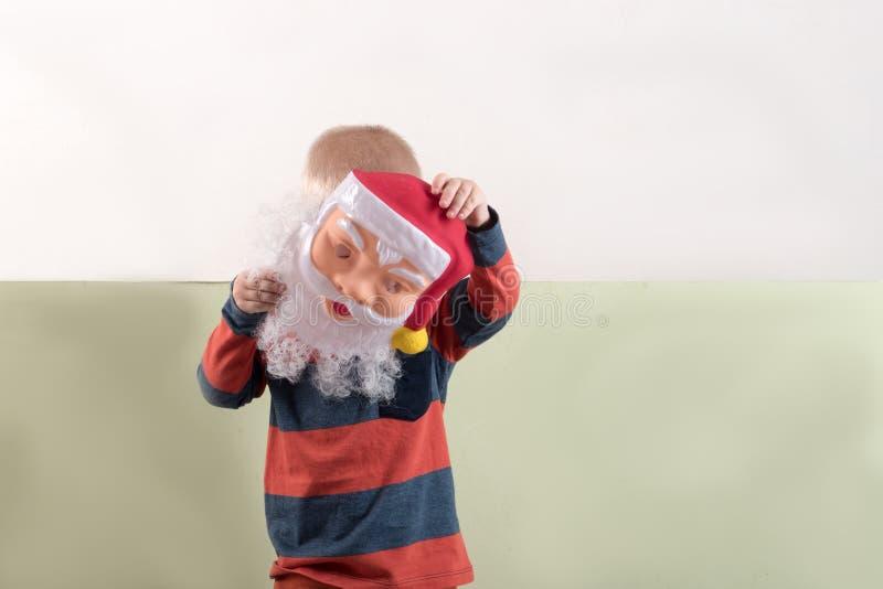 一个愉快的孩子拿着一个圣诞老人面具和一副空的横幅 与圣诞节的贺卡 圣诞节假日的概念 免版税图库摄影