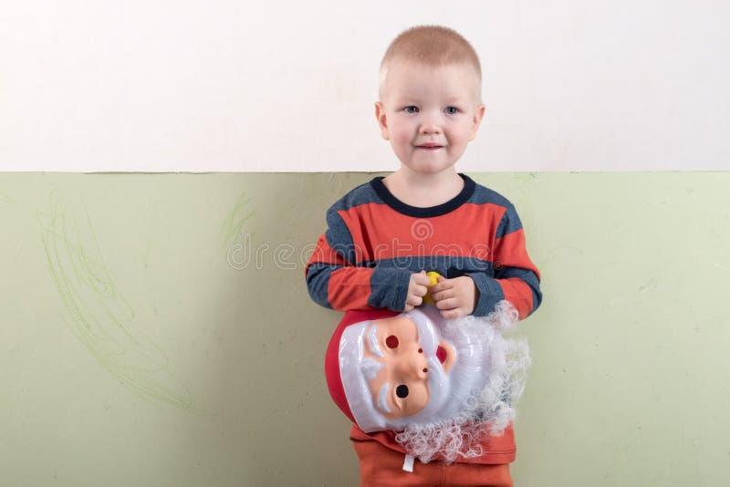 一个愉快的孩子拿着一个圣诞老人面具和一副空的横幅 与圣诞节的贺卡 圣诞节假日的概念 图库摄影