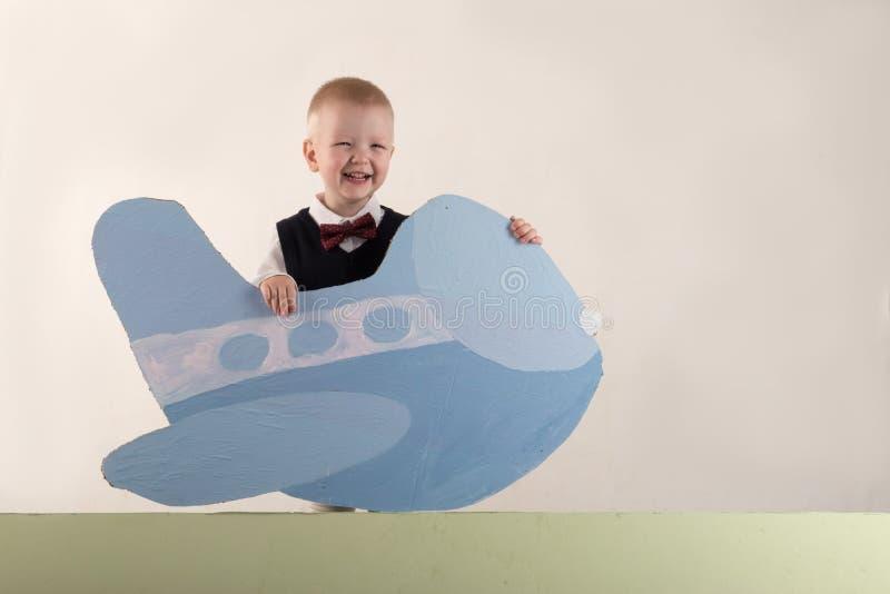 一个愉快的孩子拿着纸板飞机和一副空的横幅 与圣诞节的贺卡 圣诞节假日的概念 库存照片