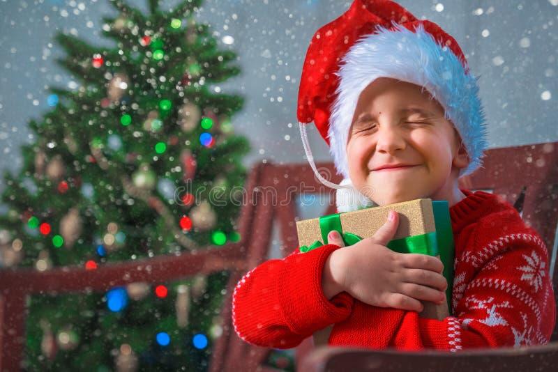 一个愉快的孩子的画象有一件礼物的在圣诞树的背景 免版税图库摄影