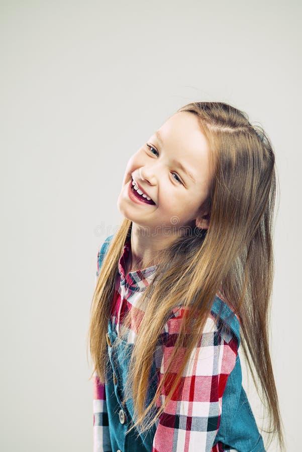 一个愉快的孩子的画象 女孩微笑并且显示情感 演播室时尚孩子射击 库存图片