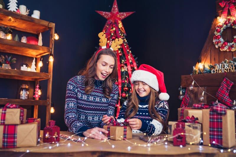 一个愉快的家庭母亲和孩子包装圣诞节礼物 库存图片