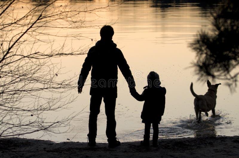 一个愉快的家庭的剪影与狗的 免版税库存图片