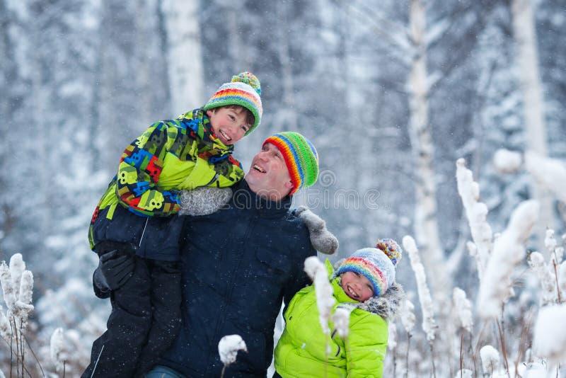 一个愉快的家庭的画象在冬天公园 父亲,儿子和一点女儿笑 免版税库存照片