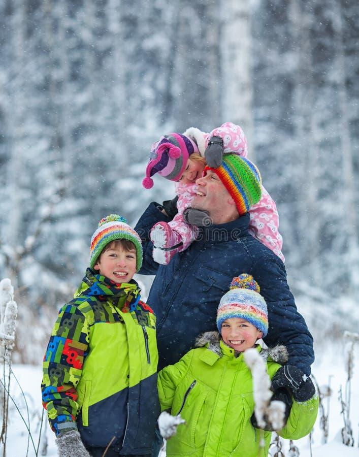 一个愉快的家庭的画象在冬天公园 父亲,儿子和一点女儿笑 免版税库存图片