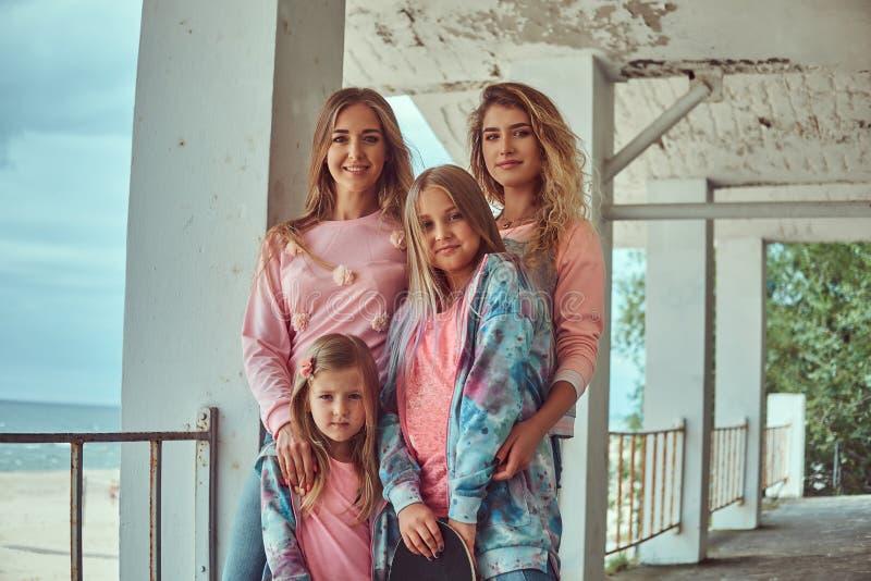 一个愉快的家庭的画象在时髦的衣裳穿戴了拿着摆在栏杆附近的滑板反对沿海 库存图片