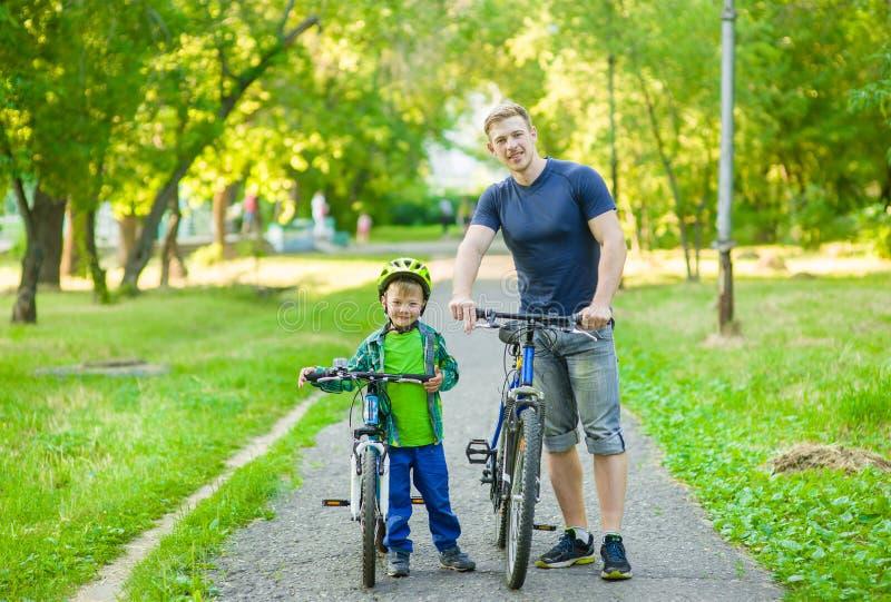 一个愉快的家庭的画象-骑自行车在公园的父亲和儿子 免版税库存照片