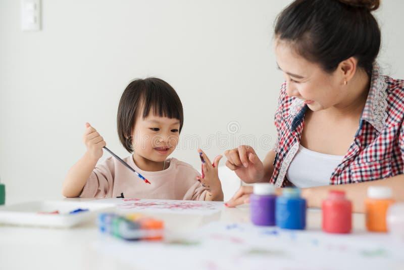 一个愉快的家庭绘 妈妈帮助她的女儿图画 免版税库存图片