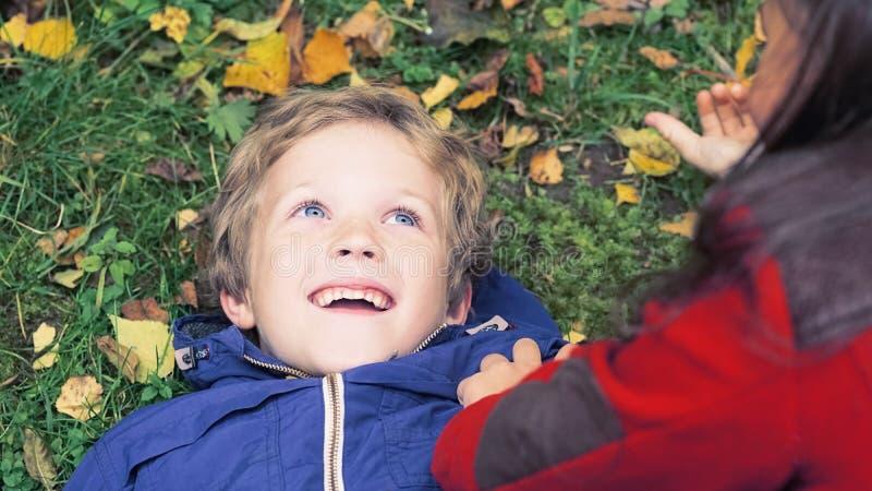 一个愉快的家庭获得乐趣在公园在秋天 家庭,爱,幸福概念 说谎的兄弟和的姐妹拥抱和 免版税库存照片