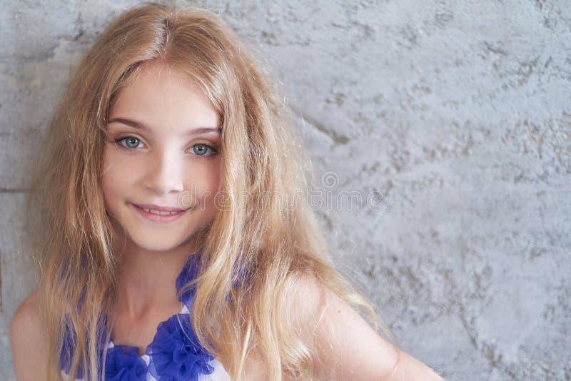 一个愉快的小女孩模型的画象与摆在演播室的迷人的微笑的 库存图片