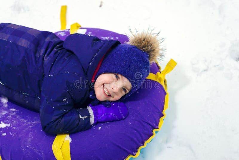 一个愉快的小男孩的冬天画象帽子的 疲乏的儿童sledding管材 免版税库存照片