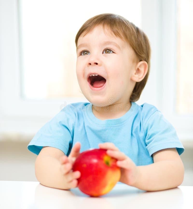 一个愉快的小男孩的画象用苹果 库存图片