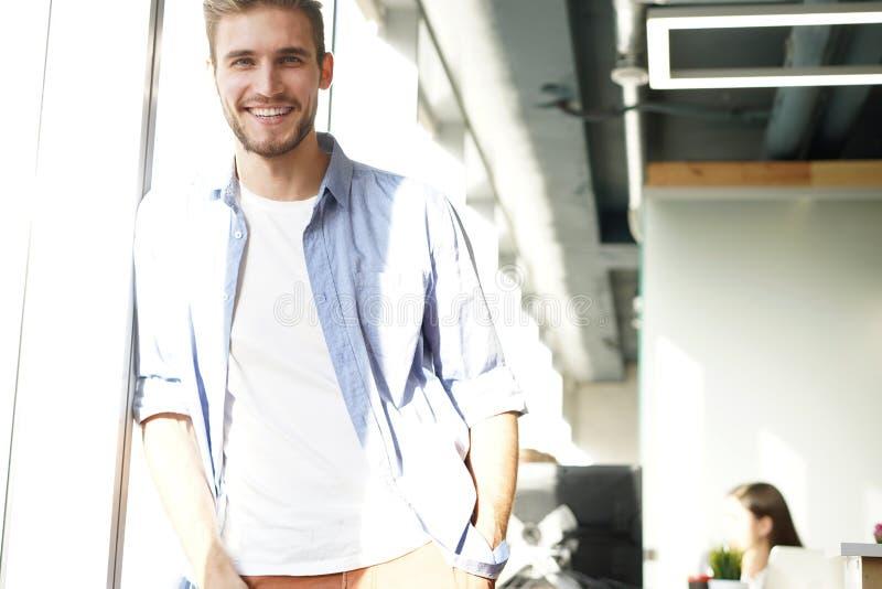 一个愉快的年轻偶然商人的画象在办公室,微笑 免版税图库摄影