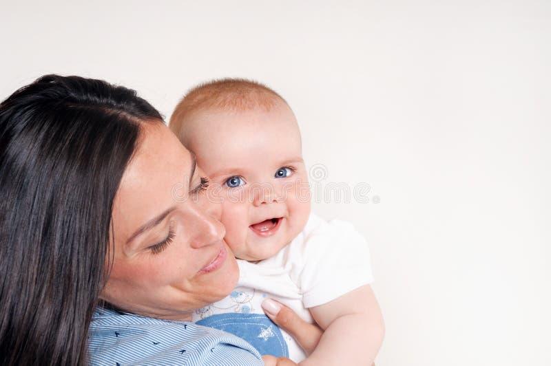 一个愉快的年轻母亲的画象在逗人喜爱的婴孩附近的 库存照片