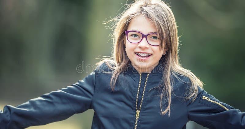 一个愉快的微笑的十几岁的女孩的画象戴牙齿括号和眼镜的 免版税库存照片
