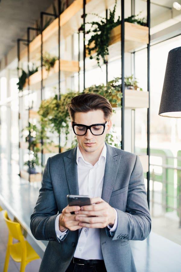 一个愉快的微笑的商人的画象在镜片的使用智能手机,当坐在办公室时 库存图片