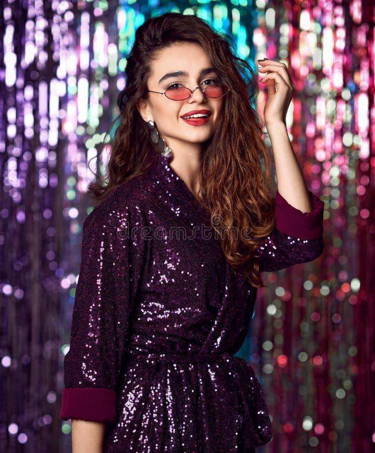 一个愉快的微笑的女孩的画象一件时髦的迷人的礼服的有在时尚党的衣服饰物之小金属片的 免版税库存照片