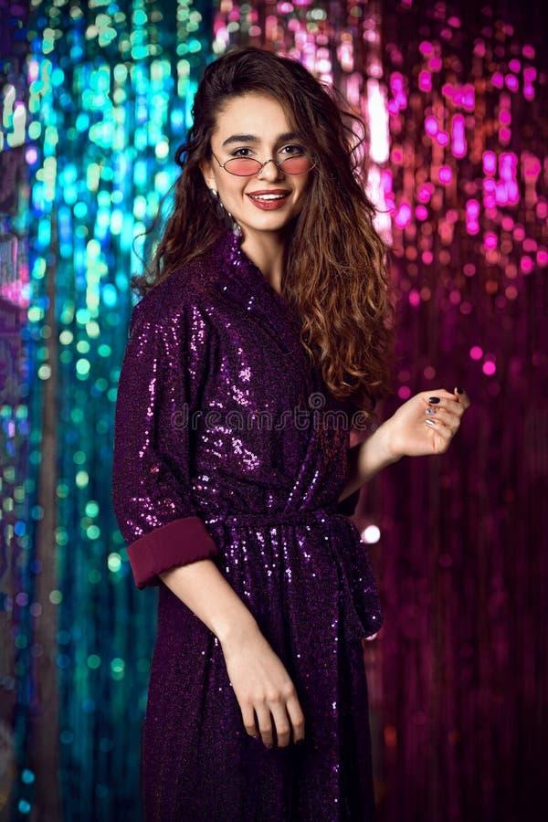 一个愉快的微笑的女孩的画象一件时髦的迷人的礼服的有在时尚党的衣服饰物之小金属片的 图库摄影